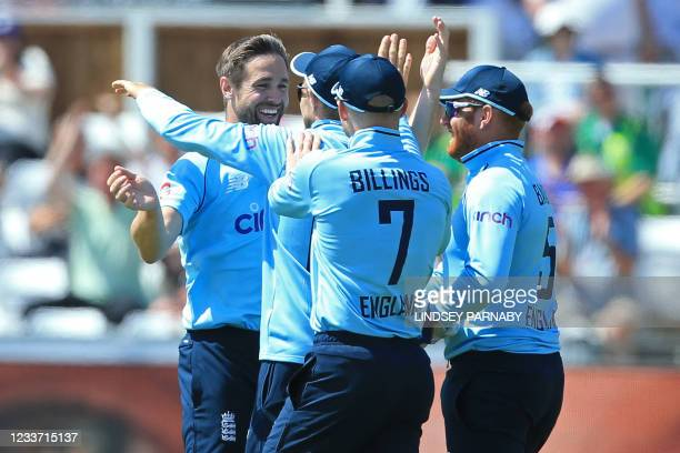 England's Joe Root celebrates with bowler England's Chris Woakes after catching out Sri Lanka's Dhananjaya Lakshan during the first one-day...