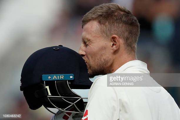 TOPSHOT England's Joe Root kisses his hat as he celebrates his century during play on the fourth day of the fifth Test cricket match between England...