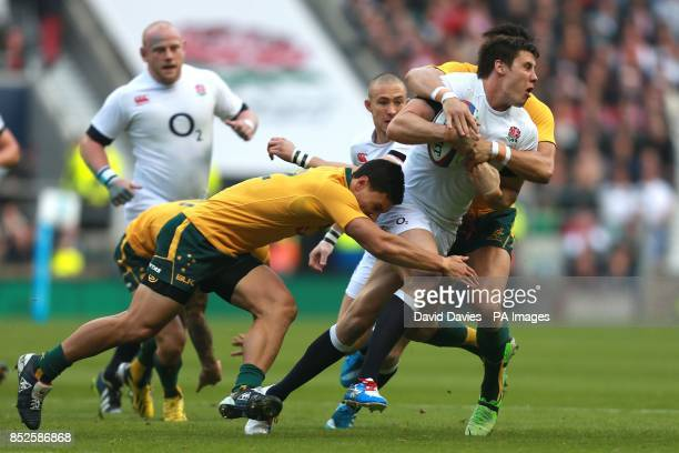 England's Joel Tomkins is tackled by Australia's Israel Folau and Adam AshleyCooper during the QBE International at Twickenham London