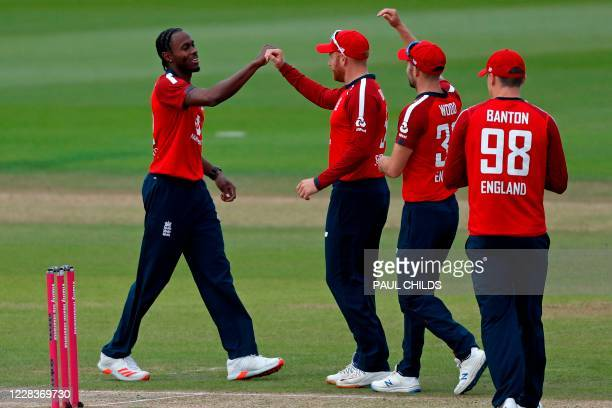 England's Jofra Archer celebrates with teammates after taking the wicket of Australia's David Warner in the first over of the international Twenty20...