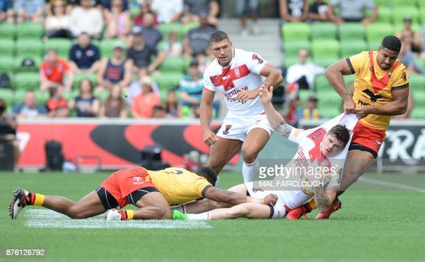 Englands John Bateman is dragged by Justin Olam and Kato Ottio of Papua New Guinea during their Rugby League World Cup quarterfinal match between...