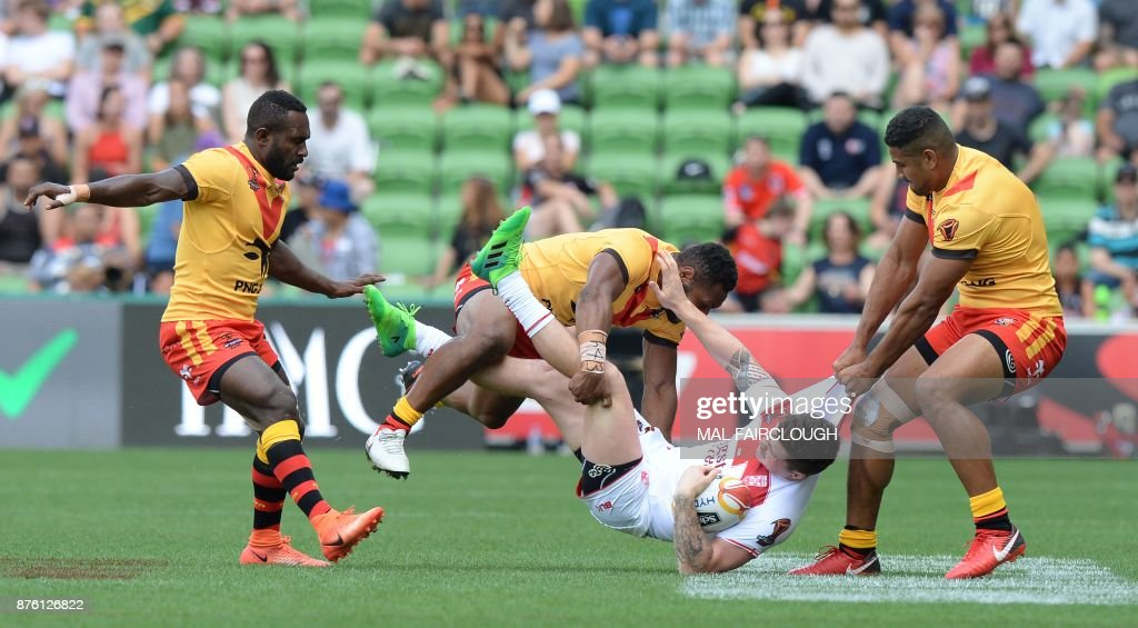 Englands John Bateman is dragged by Justin Olam and Kato Ottio of Papua New Guinea during their Rugby League World Cup quarter-final match between England and Papua New Guinea in Melbourne on November 19, 2017. / AFP PHOTO / Mal Fairclough / IMAGE