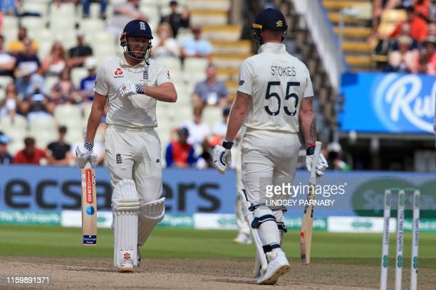 England's Jonny Bairstow indicates to England's Ben Stokes that he thought the ball hit his wrist rather than his glove as he considers a review...