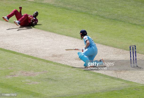 England's Jonny Bairstow reacts after falling following a bouncer from West Indies' Andre Russell during the 2019 Cricket World Cup group stage match...