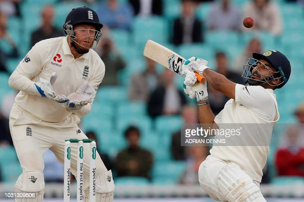 England's Jonny Bairstow reacts as India's Rishabh Pant misses a shot during play on the final day of the fifth Test cricket match between England...