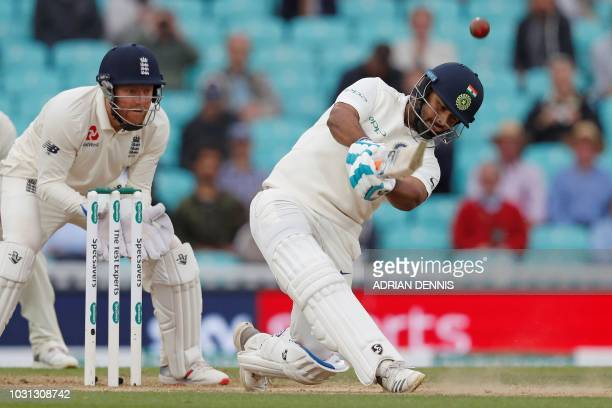 England's Jonny Bairstow watches as India's Rishabh Pant plays a shot for six runs to reach his century during play on the final day of the fifth...