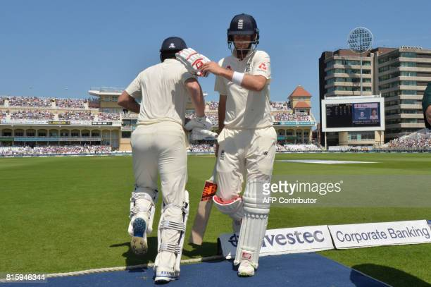England's Jonny Barstow heads out to bat as England's captain Joe Root leaves the field after being bowled out by South Africa's Chris Morris for 8...