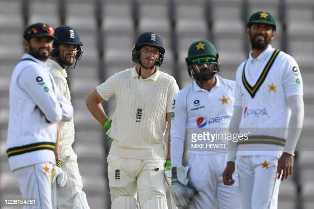 England's Jos Buttler and England's Chris Woakes wait with Pakistani players for the results of a review decision on the second day of the third Test...