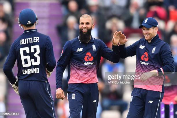 England's Jos Buttler and England's Moeen Ali celebrate with England's captain Eoin Morgan the wicket of West Indies' Marlon Samuels for 32 during...