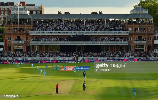 England's Jos Buttler celebrates with teammates after running out New Zealand's Martin Guptill to win the super-over to win the 2019 Cricket World...