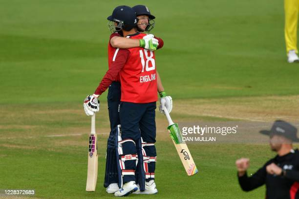 England's Jos Buttler embraces England's Moeen Ali as England celebrate their victory in the international Twenty20 cricket match between England and...