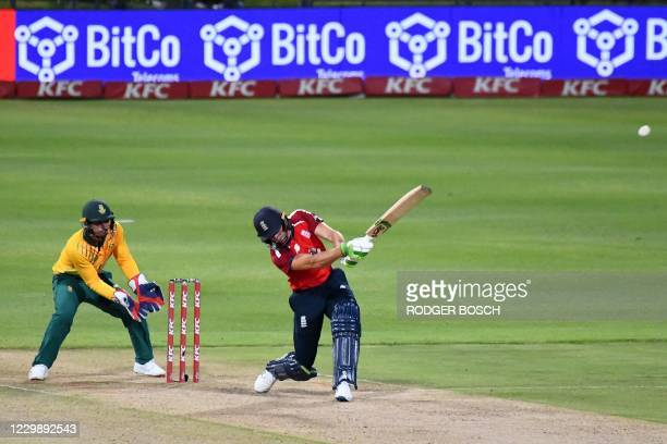 England's Jos Buttler hits a six as South Africa's captain and wicketkeeper Quinton de Kock looks on during the third T20 international cricket match...