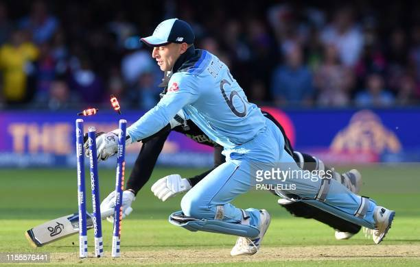 England's Jos Buttler knocks te bails off the stumps to take the wicket of New Zealand's Martin Guptill in the super over to win the 2019 Cricket...
