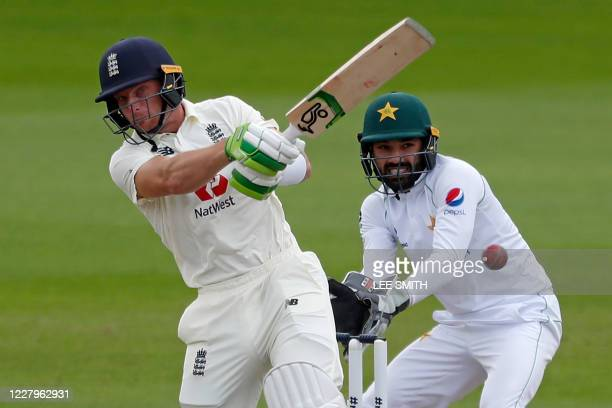 England's Jos Buttler plays a shot as Pakistan's Mohammad Rizwan keeps wicket during play on the fourth day of the first Test cricket match between...