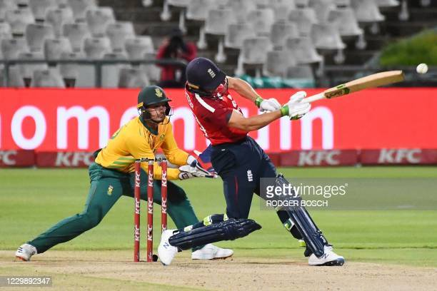 England's Jos Buttler plays a shot as South Africa's captain and wicketkeeper Quinton de Kock looks on during the third T20 international cricket...