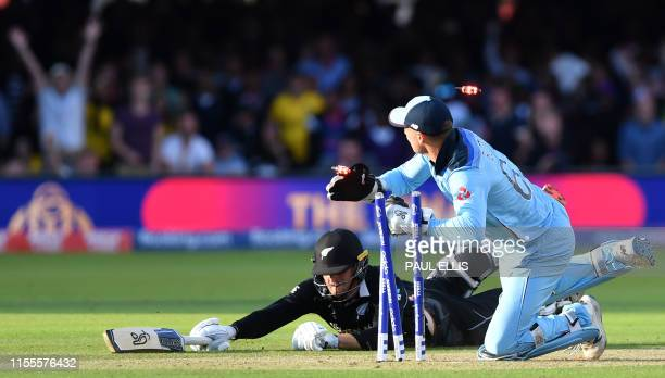 England's Jos Buttler runs out New Zealand's Martin Guptill to win the 2019 Cricket World Cup final between England and New Zealand at Lord's Cricket...