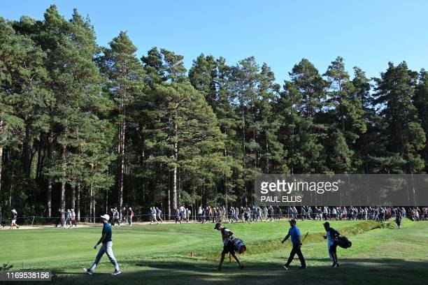 England's Justin Rose and US golfer Patrick Reed walk up the 14th fairway on day one of the golf PGA Championship at Wentworth Golf Club in Surrey...