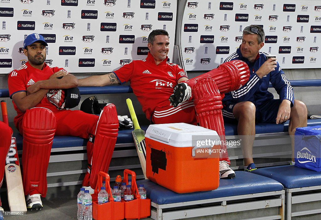 England's Kevin Pietersen (C) sits with England's Head Coach Ashley Giles (R) and England's Ravi Bopara (L) as rain delays the match during the second T20 International cricket match between England and New Zealand at The Oval cricket ground in London on June 27, 2013. Pietersen's return to England duty saw him fail to take any part in a washed-out Twenty20 match that gave New Zealand a 1-0 series win. ECB