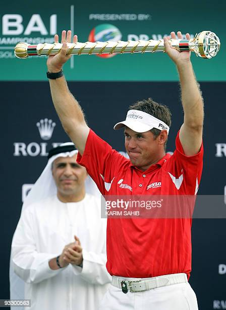England's Lee Westwood raises a trophy after winning the Dubai World Championship at the Earth Course at Jumeirah Golf Estates in Dubai on November...