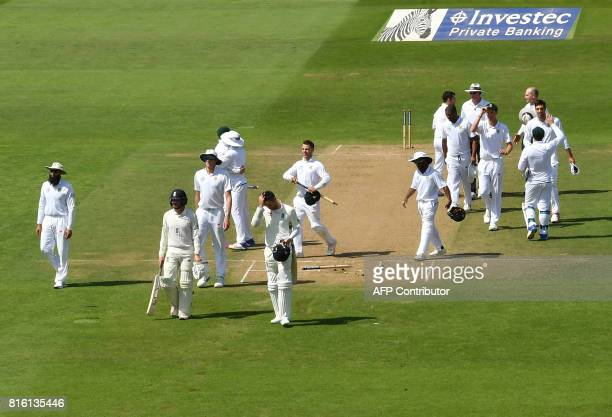 England's Liam Dawson and England's James Anderson leave the field as South Africa claim victory on the fourth day of the second Test match between...