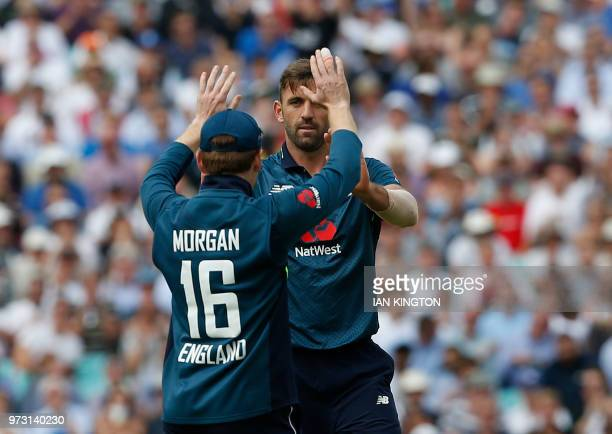 England's Liam Plunkett celebrates with England's Eoin Morgan after taking the wicket of Australia's Michael Neser for six runs during the first One...