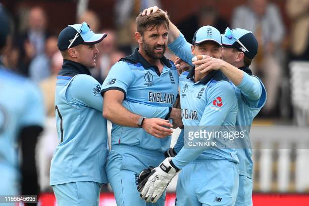 England's Liam Plunkett celebrates with England's Jason Roy and England's Jos Buttler after taking the wicket of New Zealand's Henry Nicholls for 55...