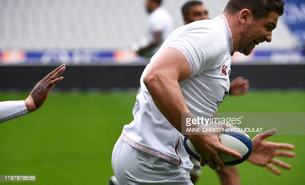 England's lock Charlie Ewels runs with the ball during the Captain's Run at the Stade de France in SaintDenis north of Paris on February 1 on the eve...