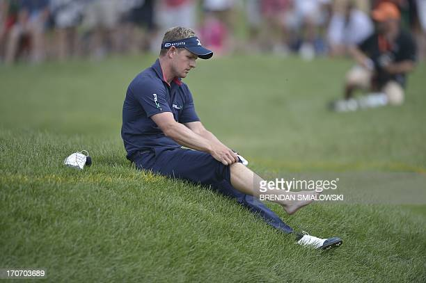 England's Luke Donald takes off sock and shoe to hit from water hazard on the fourth hole during the 4th round of the US Open at Merion Golf Club...