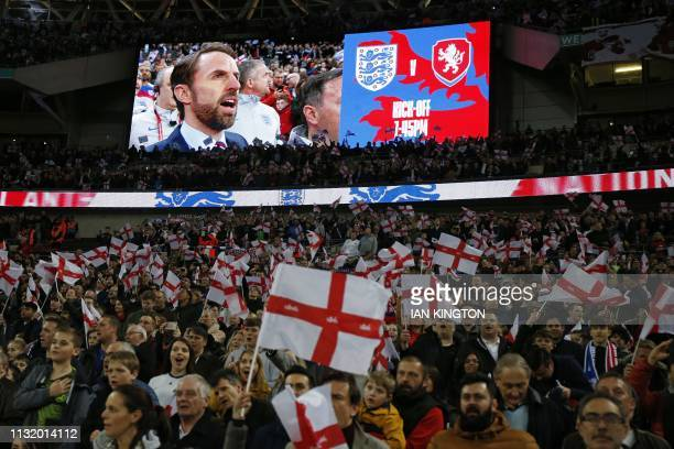 England's manager Gareth Southgate is shown on the screen as supporters wave flags during the playing of the national anthem ahead of the UEFA Euro...