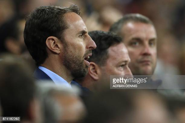 England's manager Gareth Southgate sings the National Anthem ahead of the international friendly football match between England and Brazil at Wembley...