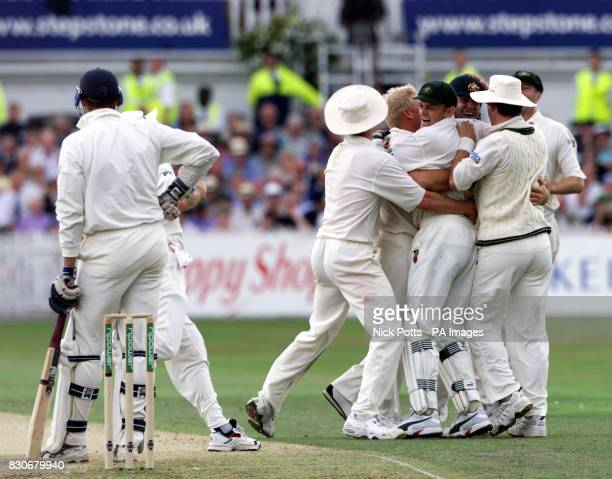 England's Marcus Trescothick stands his ground as Australia's wicketkeeper Adam Gilchrist celebrates with teammates after taking a catch that bounced...