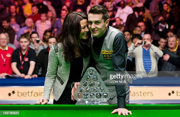 England's Mark Selby and his wife Vikki Layton pose with the trophy after defeating Australia's Neil Robertson in the Masters Snooker final at...