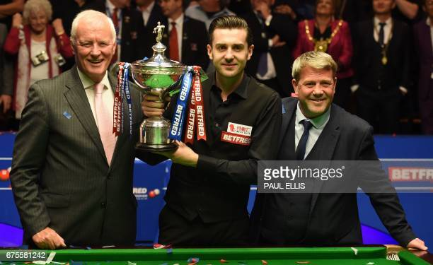 England's Mark Selby poses for a photograph with the trophy beside chairman of world snooker Barry Hearn , after beating Scotland's John Higgins in...