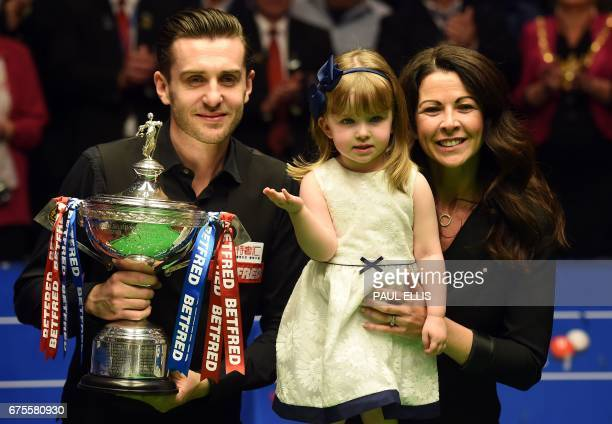 England's Mark Selby poses for a photograph with with the trophy with his daughter Sofia Maria and wife Vikki after beating Scotland's John Higgins...