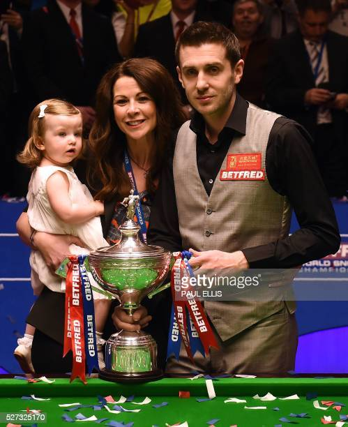 England's Mark Selby poses with wife Nikki and daughter Sophia and the trophy after beating China's Ding Junhui in the final of the World Snooker...