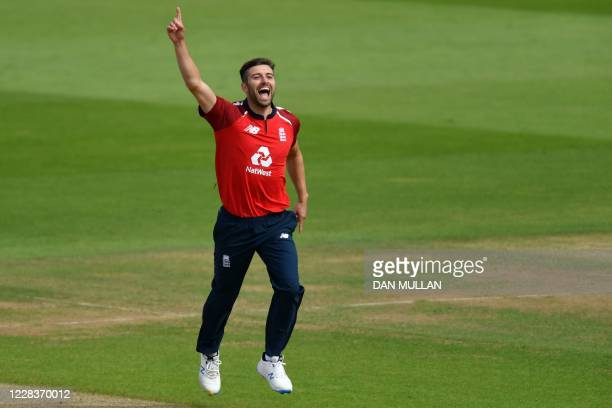 England's Mark Wood celebrates after taking the wicket of Australia's wicket keeper Alex Carey in the second over of the international Twenty20...