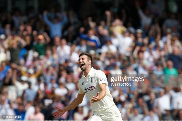 England's Mark Wood celebrates after taking the wicket of India's Rohit Sharma for 21 runs on the fourth day of the second cricket Test match between...