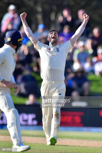 England's Mark Wood celebrates New Zealand's Colin de Grandhomme being caught during day five of the second cricket Test match between New Zealand...