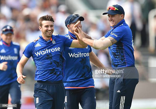 England's Mark Wood celebrates with Joe Root and Jason Roy after taking the wicket of Pakistan's Shoaib Malik during play in the second one day...