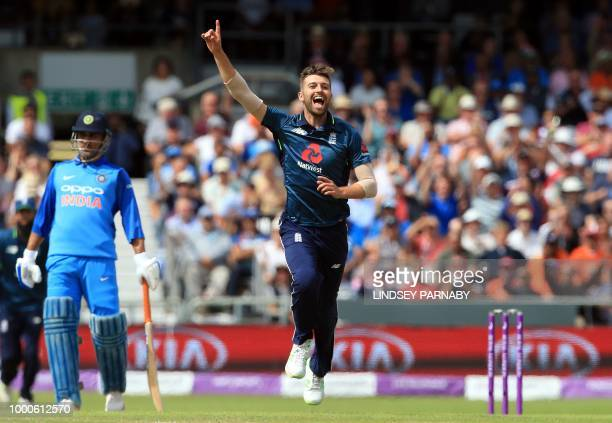 England's Mark Wood celebrates with team mates after England's Jos Buttler took the wicket of India's Hardik Pandya for 21 runs during the third One...