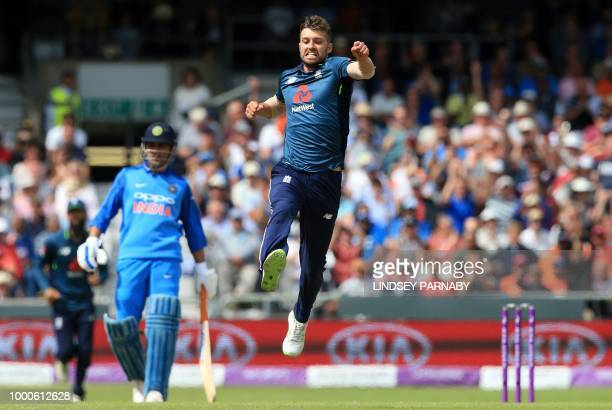 TOPSHOT England's Mark Wood celebrates with team mates after England's Jos Buttler took the wicket of India's Hardik Pandya for 21 runs during the...