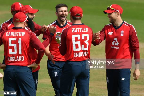 England's Mark Wood celebrates with teammates after taking the wicket of Australia's wicket keeper Alex Carey in the second over of the international...
