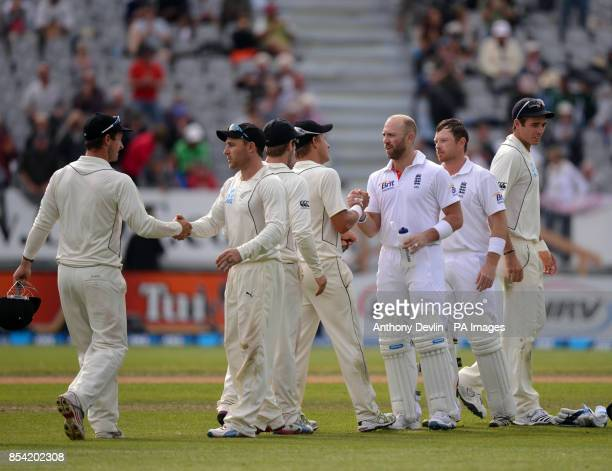 England's Matt Prior and Ian Bell shake hands with New Zealand players as the match is drawn during Day Five of the First Test at the University Oval...
