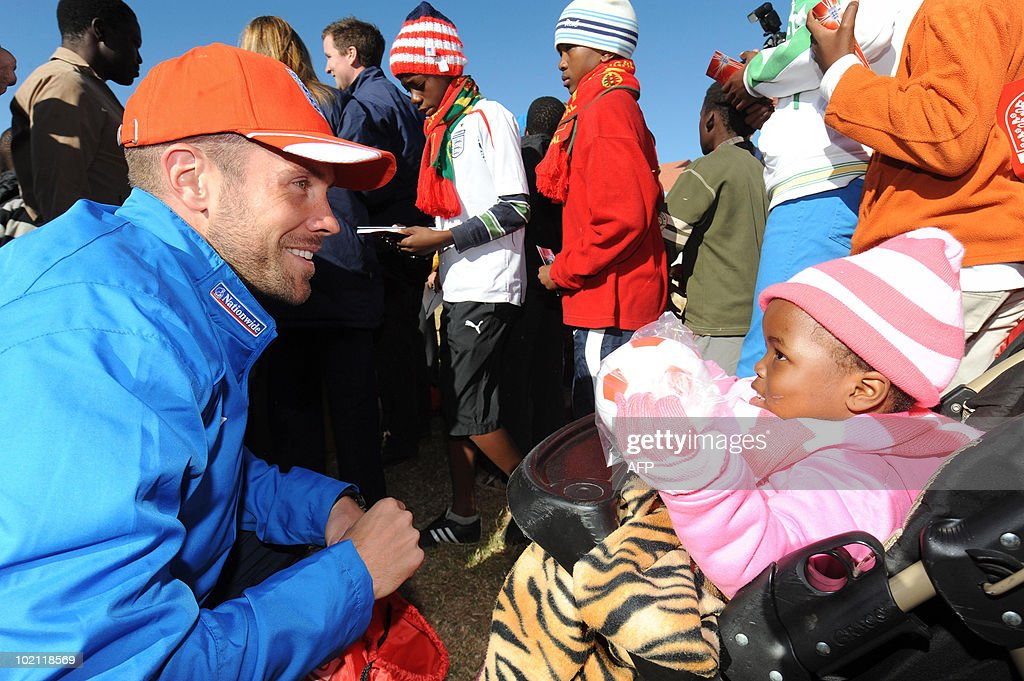 England's Matthew Upson greets a child during a visit to an orphanage in Tihabane Township near, Rustenburg on June 15, 2010.