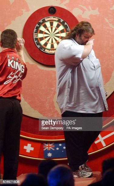 England's Mervyn King in action as Andy Fordham shows his despair during the Final of the Lakeside World Professional Darts Championships at the...