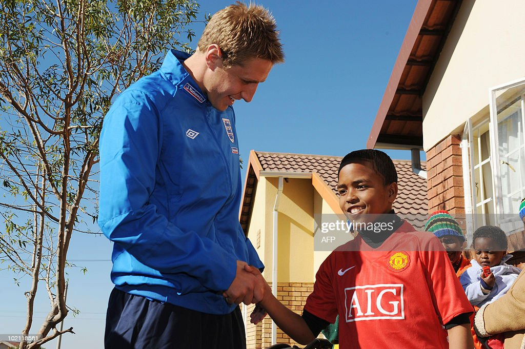 England's Michael Dawson greets a child during a visit to an orphanage in Tihabane Township near, Rustenburg on June 15, 2010.