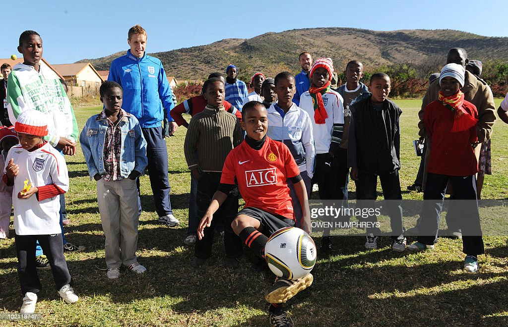 England's Michael Dawson lokks at a child play with a football during a visit to the Tlhabane Township near Rustenburg, South Africa on June 15, 2010.