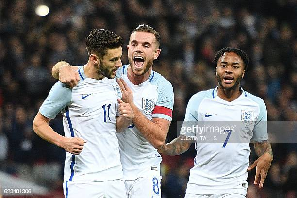 England's midfielder Adam Lallana celebrates scoring his team's first goal from the penalty spot with England's midfielder Jordan Henderson and...