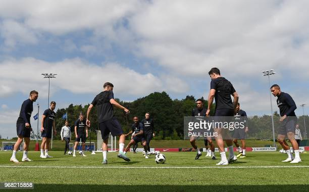 England's midfielder Adam Lallana passes the ball to England's defender Trent AlexanderArnold during a open training session at St George's Park in...