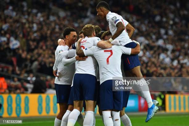 England's midfielder Alex OxladeChamberlain celebrates with teammates after scoring the opening goal of the UEFA Euro 2020 qualifying first round...